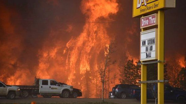 A wall of fire rages outside of Fort McMurray, Alta. Tuesday May 3, 2016. (Terry Reith/THE CANADIAN PRESS)