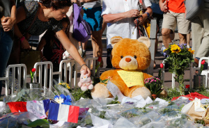 A womanj places a stuffed toy alongside flowers, flags and a large stuffed toy in tribute to victims. (Photo credit: Pascal Rossignol/Reuters)