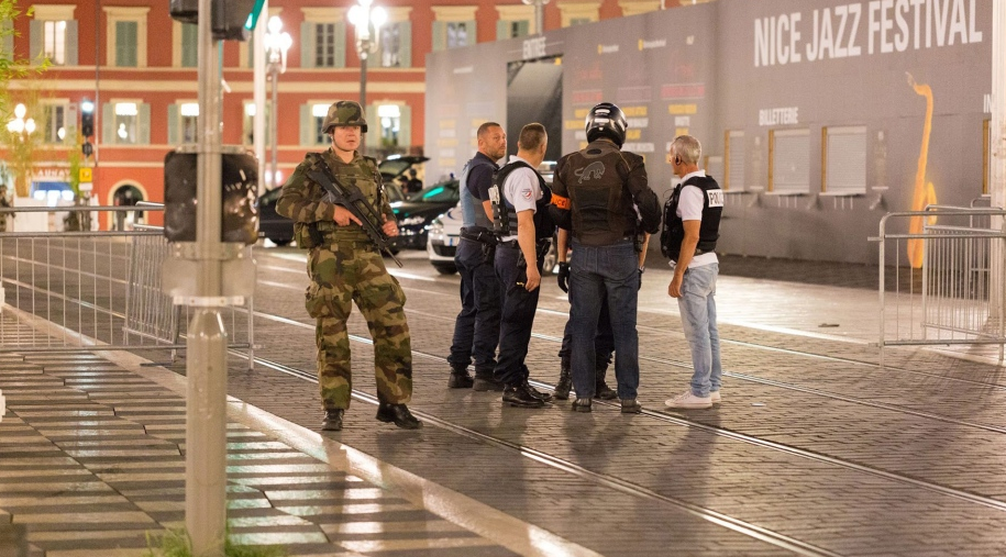 Police officers and a soldier stand by the sealed off area of an attack on Nice, southern France, on Friday, July, 15, 2016. (AP Photo/Ciaran Fahey)