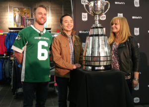 Rider Rob Bagg, the CFL's Christina Litz and Mark's David Lui pose with Grey Cup